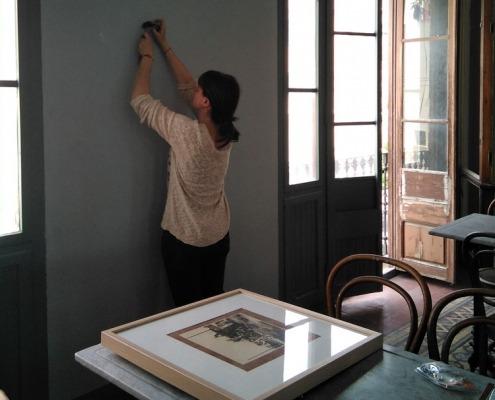 Laura penjant quadre a la sala de la Societat